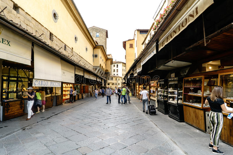 : View of the businesses located to the sides of the Bridge on the river Arno, called `Ponte Vecchio` with people walking royalty free stock images