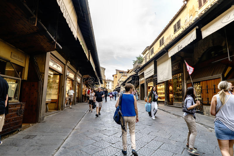 : View of the businesses located to the sides of the Bridge on the river Arno, called `Ponte Vecchio` with people walking stock photos