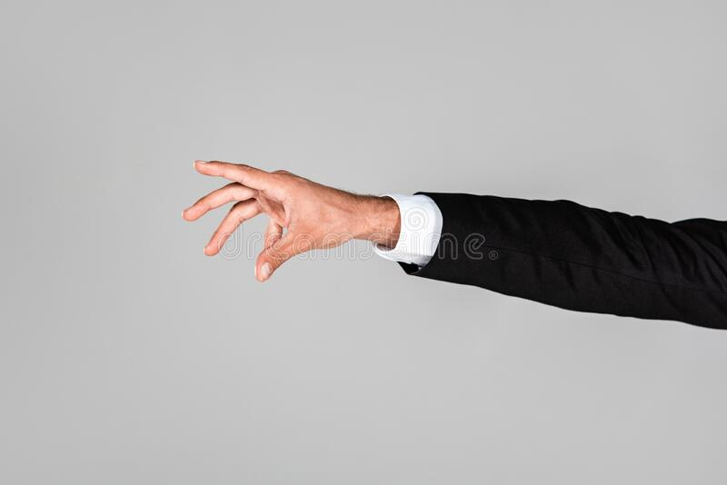 View of businessman hand gesturing isolated on grey. Cropped view of businessman hand gesturing isolated on grey stock photography