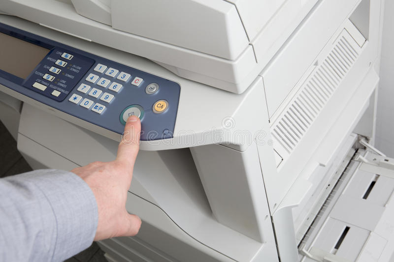 View of businessman pressing printer's button in office royalty free stock images
