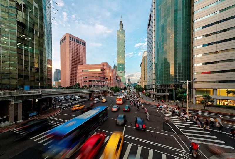 View of a busy street corner in Downtown Taipei City at rush hour with cars & buses dashing by stock photo