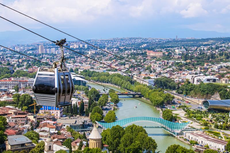 View of cable car above Tbilisi Georgia with view of Mtkvari - Kura River and Peace Bridge and city with mountains in the distance.  royalty free stock image