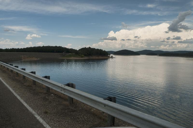 View of a calm and serene lake with approaching storms. Stormy weather is approaching a serene lake with hills, islands, trees and bouys. Broken Bow Lake and Dam royalty free stock photos