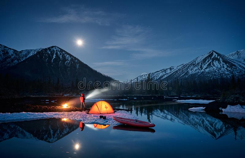 View of camp life in a mountain terrain. Lake shore with canoe. View of camp life. Man having a rest near campfire and orange tent next lake shore at moonlight stock images