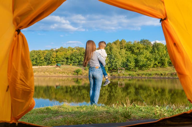 View from the camping tent. Girl enjoys nature holding child in her hands. Hiking with child royalty free stock images