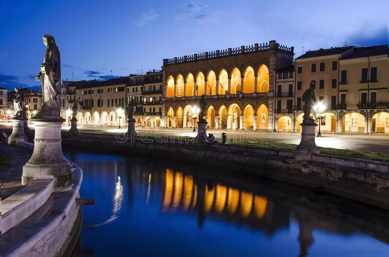 View of the canal with statues on square of Prato della Valle in Padova after sunset, Italy. View of the basilica on Prato della Valle in Padova at night royalty free stock photo
