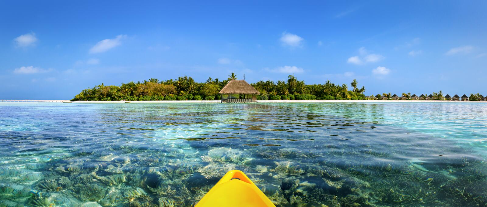View from a canoe over coral gardens to an Maldivian island royalty free stock images