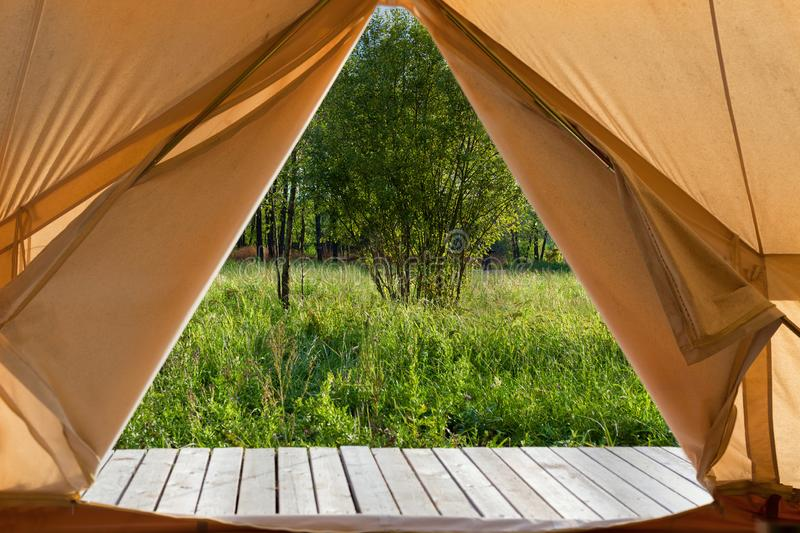 View from the canvas tent upon the green meadow stock photography