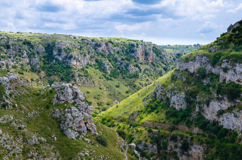 View of canyon with rocks and caves Murgia Timone, Matera Sassi,. View of ravine canyon with rocks and caves di Murgia Timone near old ancient town Matera Sassi royalty free stock photography