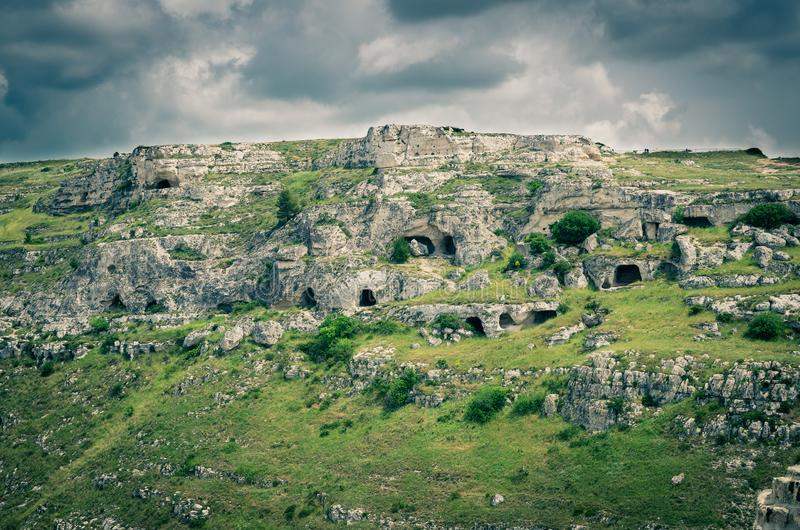 View of canyon with rocks and caves Murgia Timone, Matera Sassi, Italy. View of ravine canyon with rocks and houses in caves di Murgia Timone near old ancient stock photography