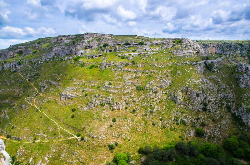 View of canyon with rocks and caves Murgia Timone, Matera Sassi, Italy. View of ravine canyon with rocks and houses in caves di Murgia Timone near old ancient royalty free stock images