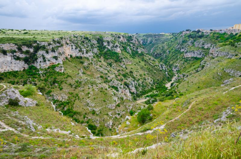 View of canyon with rocks and caves Murgia Timone, Matera Sassi,. View of river valley with ravine canyon, rocks, green grass, path, caves di Murgia Timone and stock photos