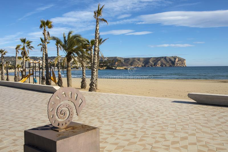 View of Cap de Sant Antoni from Arenal Beach in Xabia. XABIA, SPAIN - APRIL 12TH 2018: A bronze sea shell sculpture located on the promenade along the Arenal in stock image