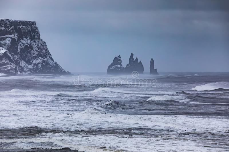 View from cape Dyrholaey on Reynisfjara Beach, Iceland. View from cape Dyrholaey on Reynisfjara Beach and Reynisdrangar basalt sea stacks, Iceland. Winter storm royalty free stock images