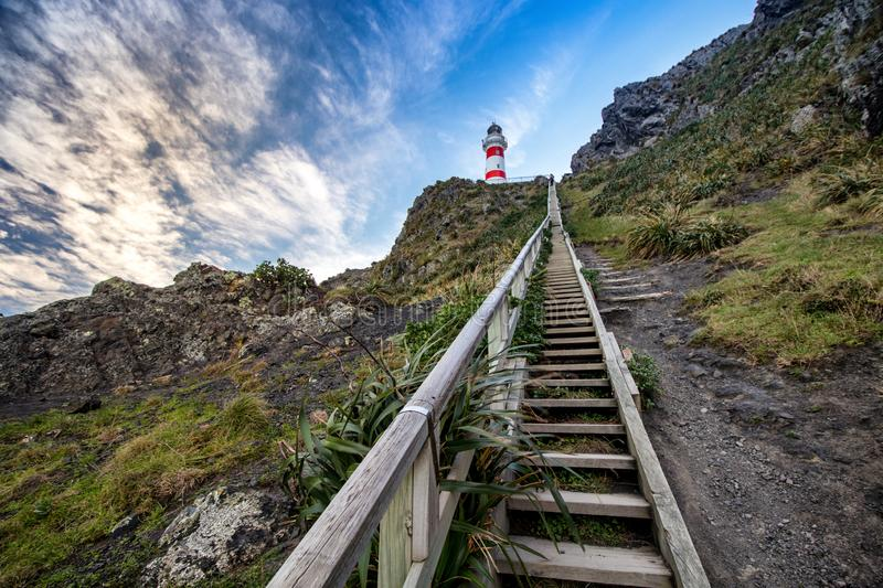 View on Cape Palliser red and white striped lighthouse with steep wooden stairs leading to it royalty free stock photography