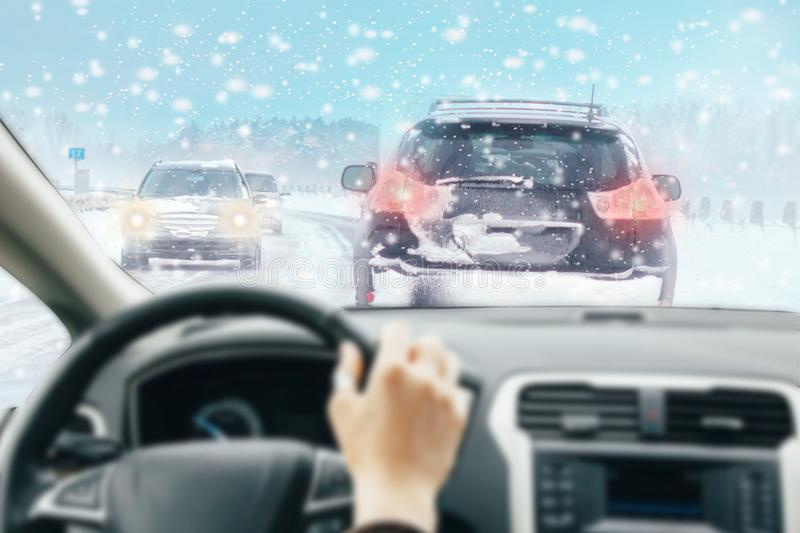 View from car inside with part of interior with driver male hand on the steering wheel during bright snowy winter day on straight. Ice road with snowy vehicles royalty free stock photo