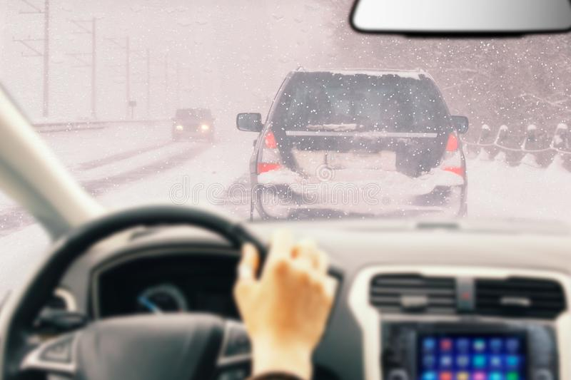 View from car inside with part of interior with driver male hand on the steering wheel during bright snowy winter day on straight. Ice road with snowy vehicles royalty free stock photos