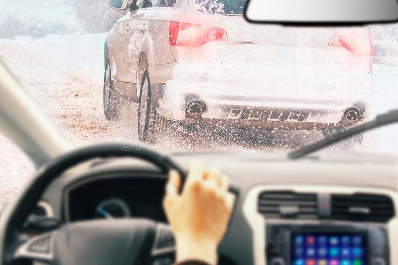 View from car inside with part of interior with driver male hand on the steering wheel during bright snowy winter day on straight. Ice road with snowy vehicles royalty free stock image