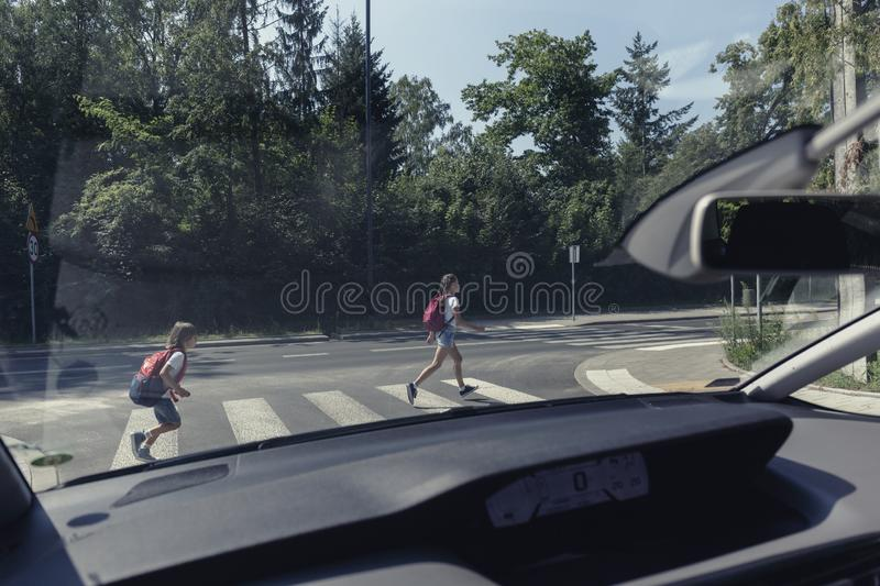 View from a car on kids running through crosswalk to the school stock photography
