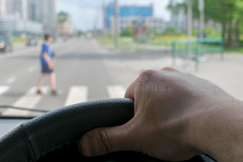 View from the car, the man`s hand on the steering wheel of the car, located opposite the pedestrian crossing. And pedestrians crossing the road royalty free stock photos