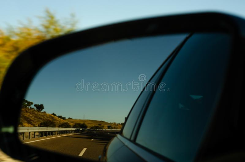 View in the car mirror on fast road in the Spain, beautiful landscape stock photography