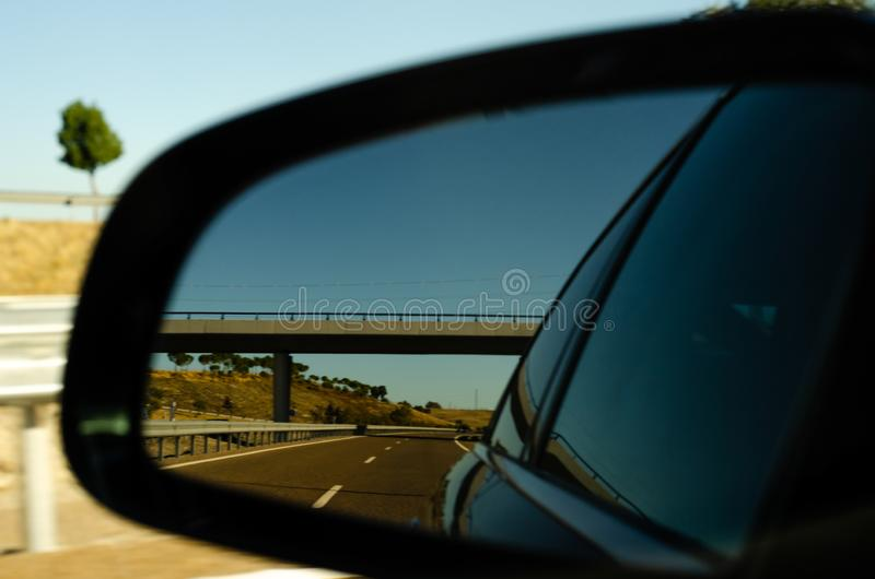 View in the car mirror on fast road in the Spain, beautiful landscape royalty free stock photo