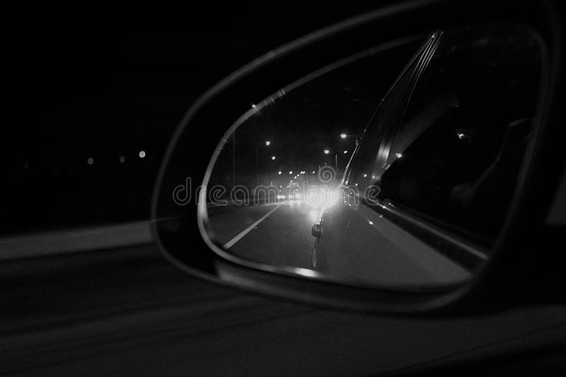 View from a car mirror. Long distance drive by car and views from a mirror stock photo