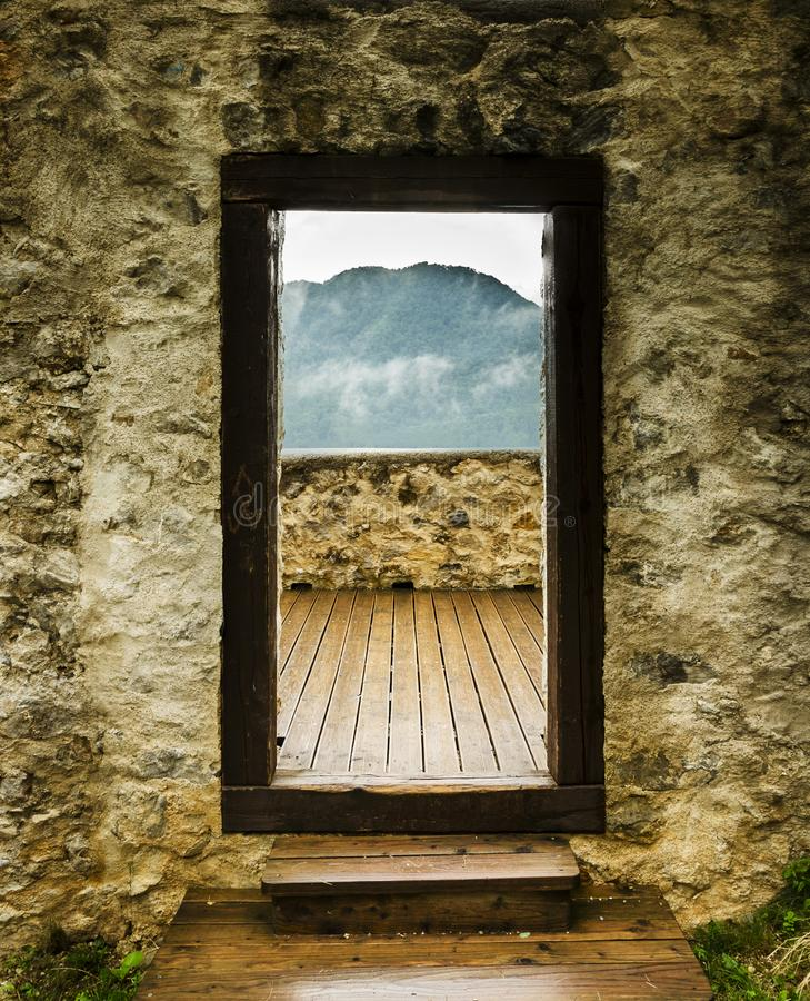 View through the castle door to the mountains. View through the castle door to the misty mountains stock photo