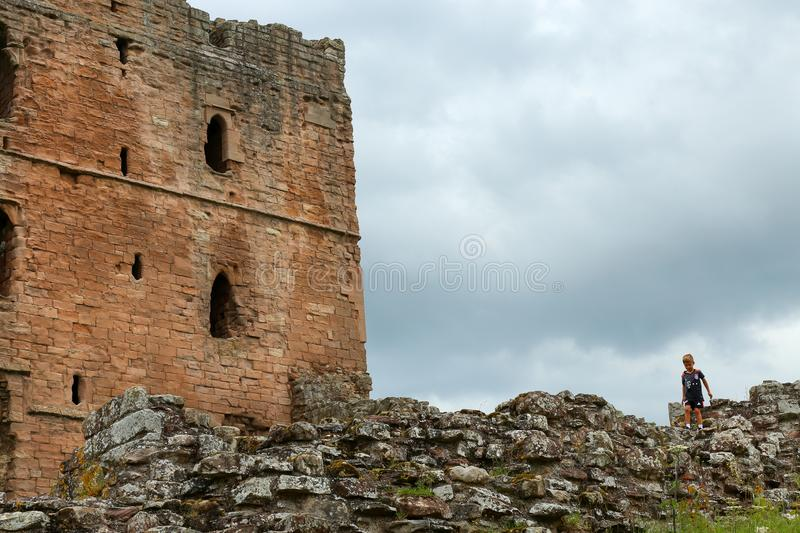View of a castle tower with the stone wall and a child on walking on royalty free stock images