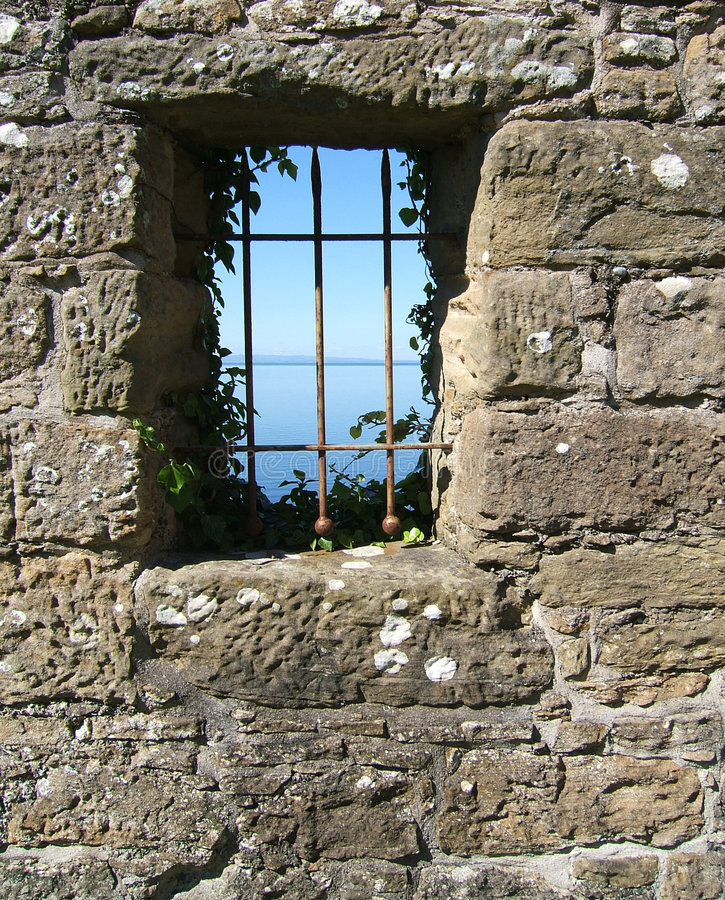 View from a castle window. Looking out to sea through the ivy-clad iron bars of a Scottish castle window stock photography