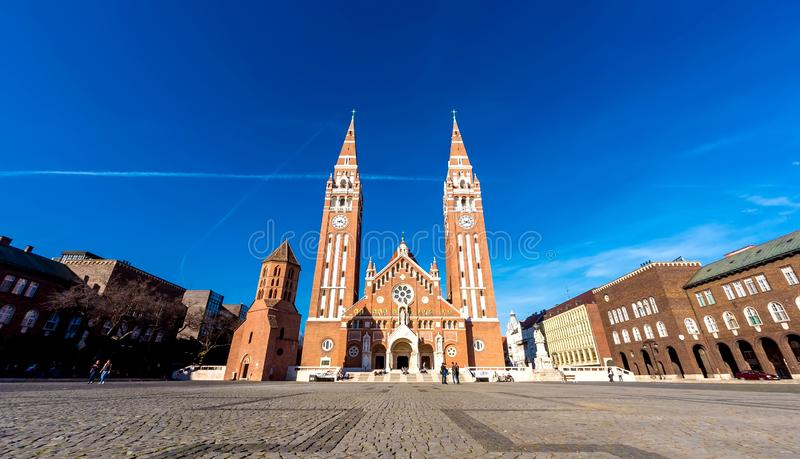 View on the Cathedral of Szeged, Hungary. SZEGED, HUNGARY - CIRCA APRIL 2019: View on the famous Cathedral as visitors pass by at the church circa April 2019 in royalty free stock photos