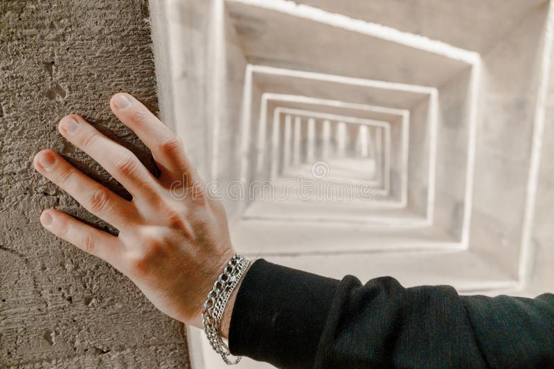 View on caucasian mans hand with bracelets touch the wall. He standing, peek and thinking about future and choice of direction. Challenge of path way to royalty free stock images