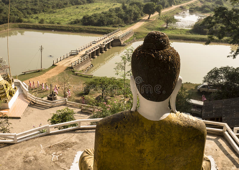 View from a cave temple near Hpan. Buddha statue with a view to the lake, nons passing by, Hpan, Myanmar royalty free stock images