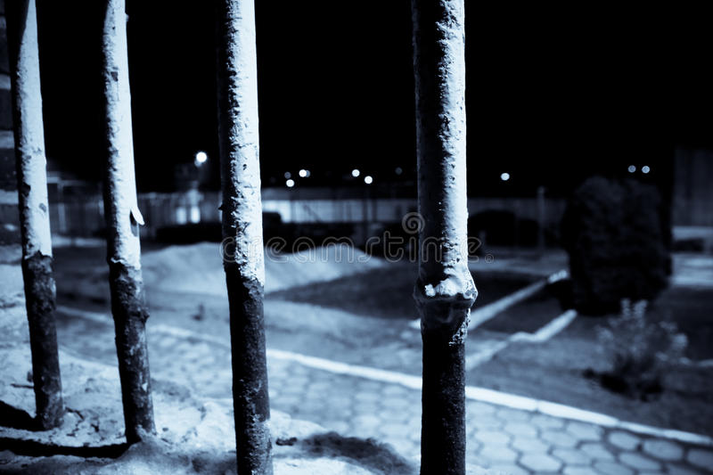 View from a cell during night. Rusty bars intersecting a view seen from a prison cell royalty free stock photo