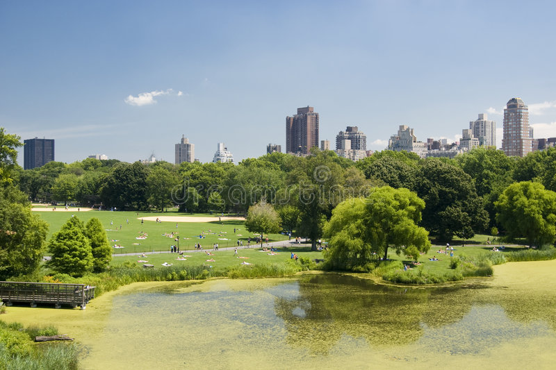 View from Central Park. With lake, trees and people having pic-nic in a sunny day with clouds - New york downtown skyline - New York 2007 stock photo