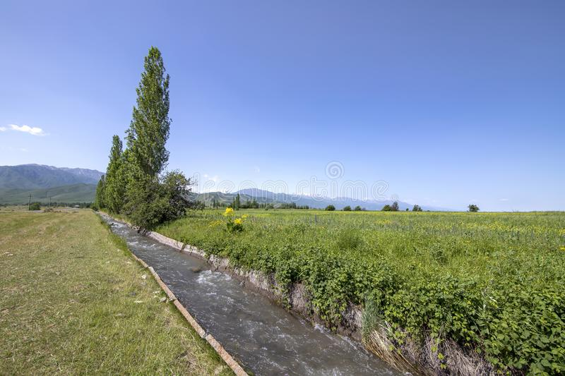 View of the central Tien Shan mountains in Kyrgyzstan with flowing water in the aryk and green fields royalty free stock photography