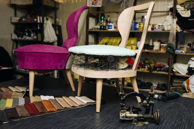 Detail from the upholstery workshop. View at chair repairing in the upholstery workshop stock photo