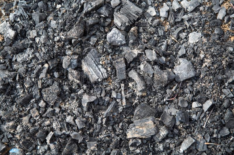 View of charcoal remaining after the fire, with nails. Backgrounds stock image