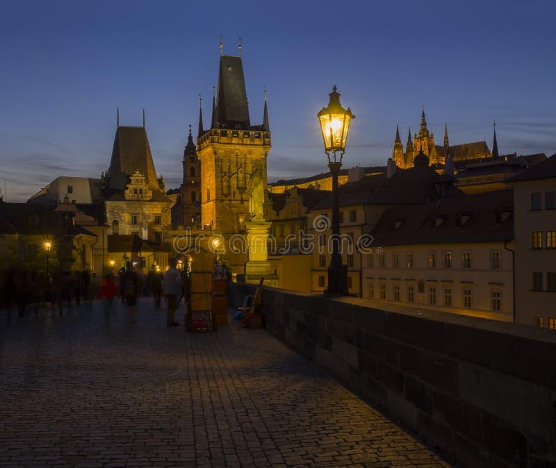 View from Charles Bridge on Mala Strana bridge tower with glowing street lamp nad Prague Castle at night, dark blue sky royalty free stock photos