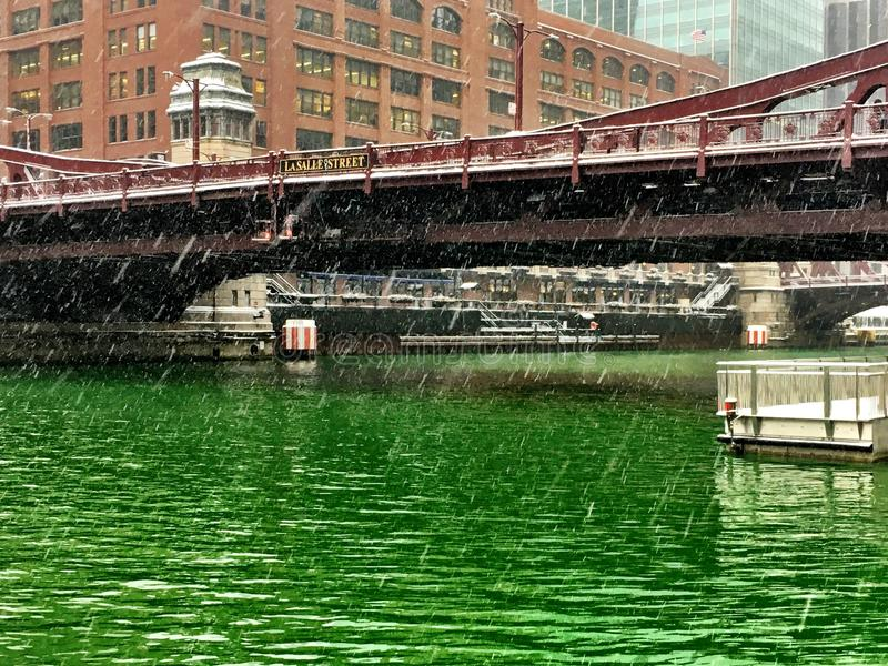 View of Chicago River after being dyed green for St. Patrick& x27;s Day, with snow showers coming down. Downtown Chicago - the Chicago River is traditionally royalty free stock image