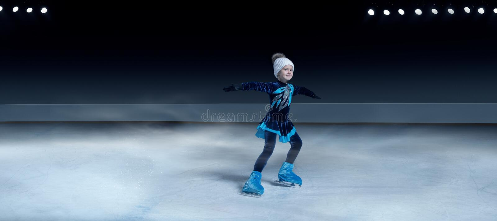 child  figure skater on dark ice arena background royalty free stock photography