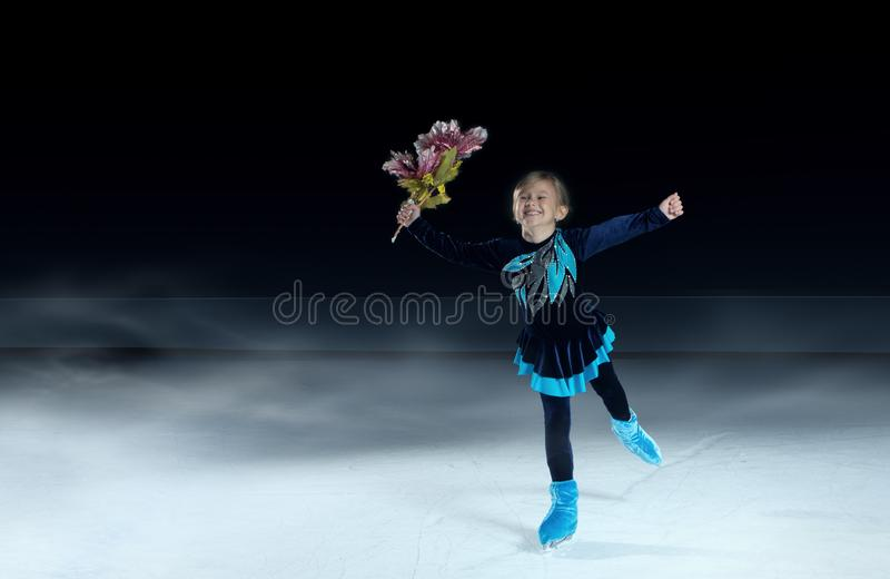 Child  figure skater on dark ice arena background stock photography