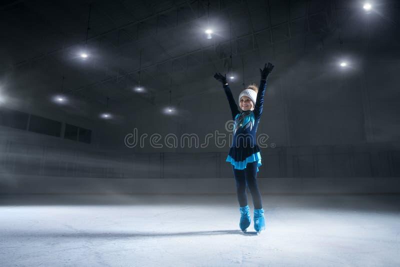 View of child  figure skater on dark ice arena stock photos