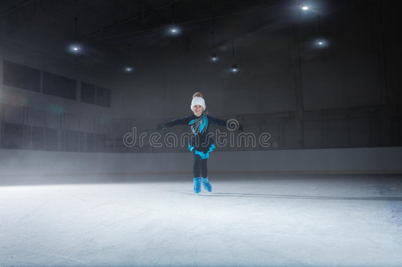 View of child  figure skater on dark ice arena stock photography