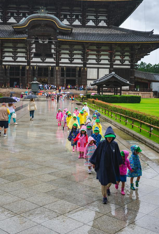 A school excursion in rain in front of the Todaji-ji temple in Nara, Japan. View of a children in a school excursion in colorful raincoats in front of the Todaji stock photo