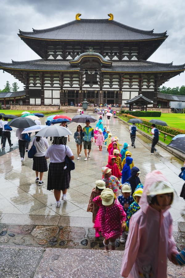 A school excursion in rain in front of the Todaji-ji temple in Nara, Japan. View of a children in a school excursion in colorful raincoats in front of the Todaji stock images