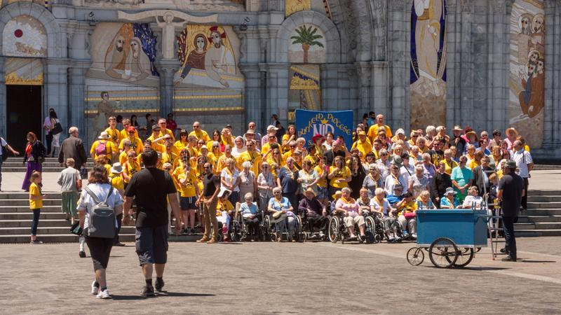 View on the Christian pilgrims during the photo session in the Sanctuary of Our Lady of Lourdes. The Hautes-Pyrenees department in the Occitanie region in royalty free stock image