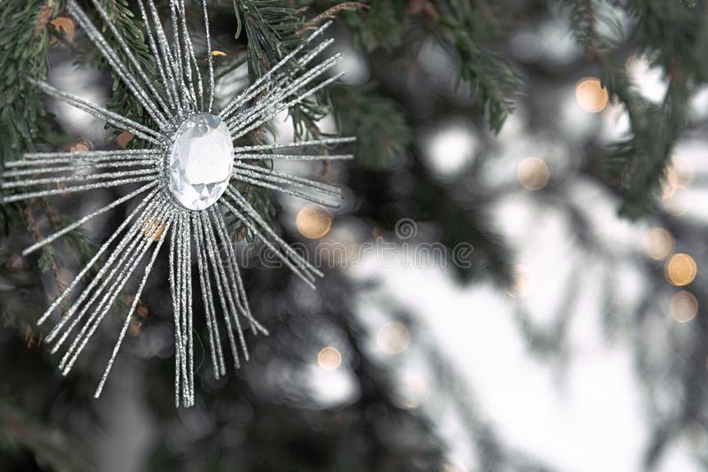 View of a Christmas toy in the form of the sun that sees on the branches of spruce. Christmas concept, decor, lifestyle royalty free stock photo