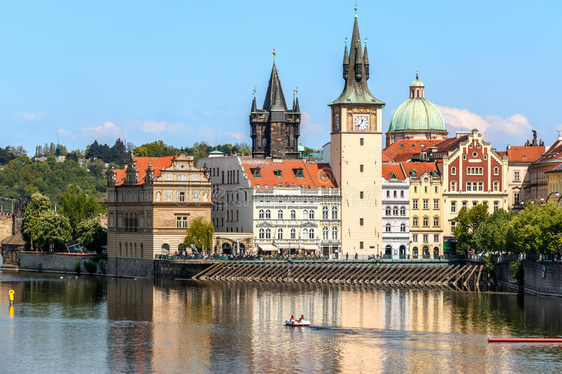 View of the church clock in Prague with the Vltava river in front stock photography