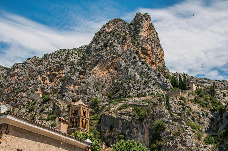 View of the church Notre-Dame de Beauvoir amid the cliffs and steeple of Moustiers-Sainte-Marie. stock image